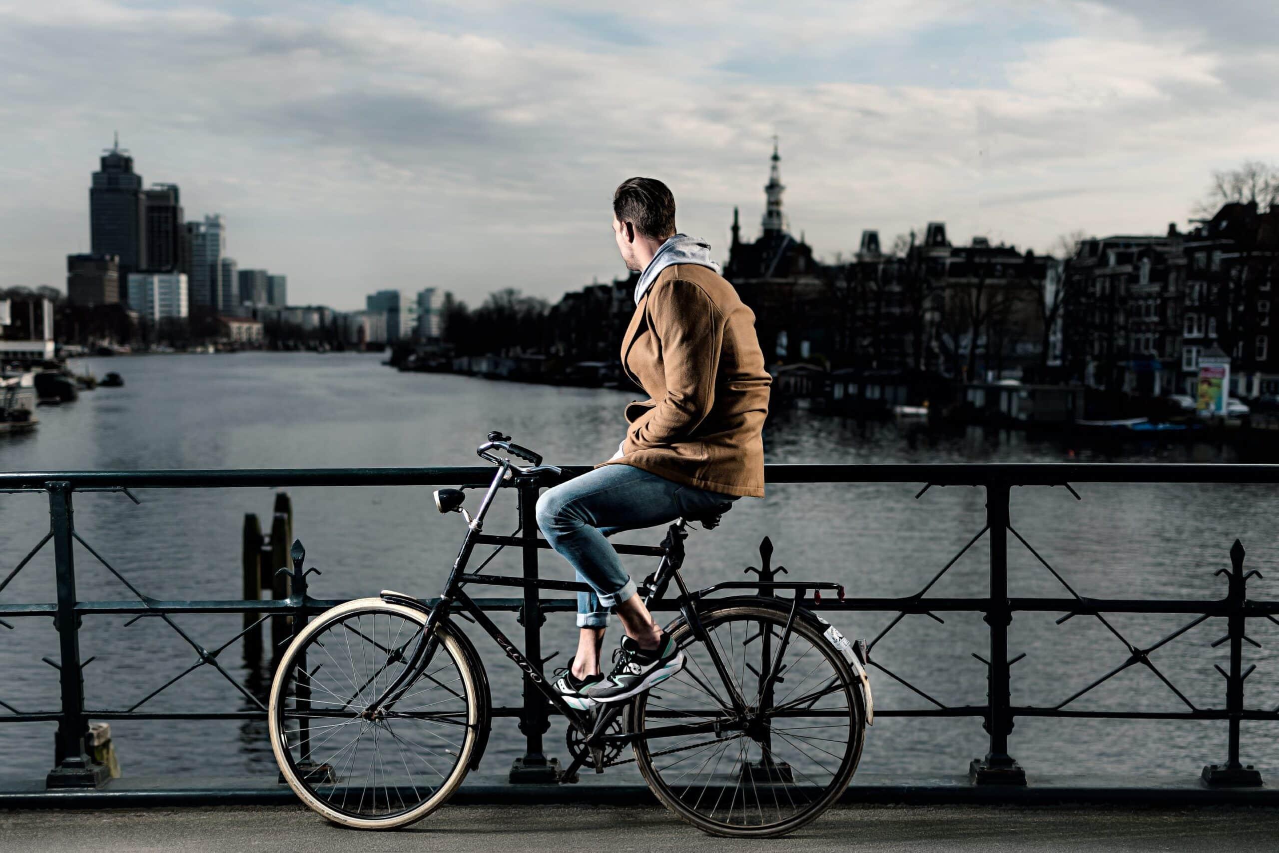 Portretfoto van mannelijk model op de berlage burg in amsterdam met stadsfiets