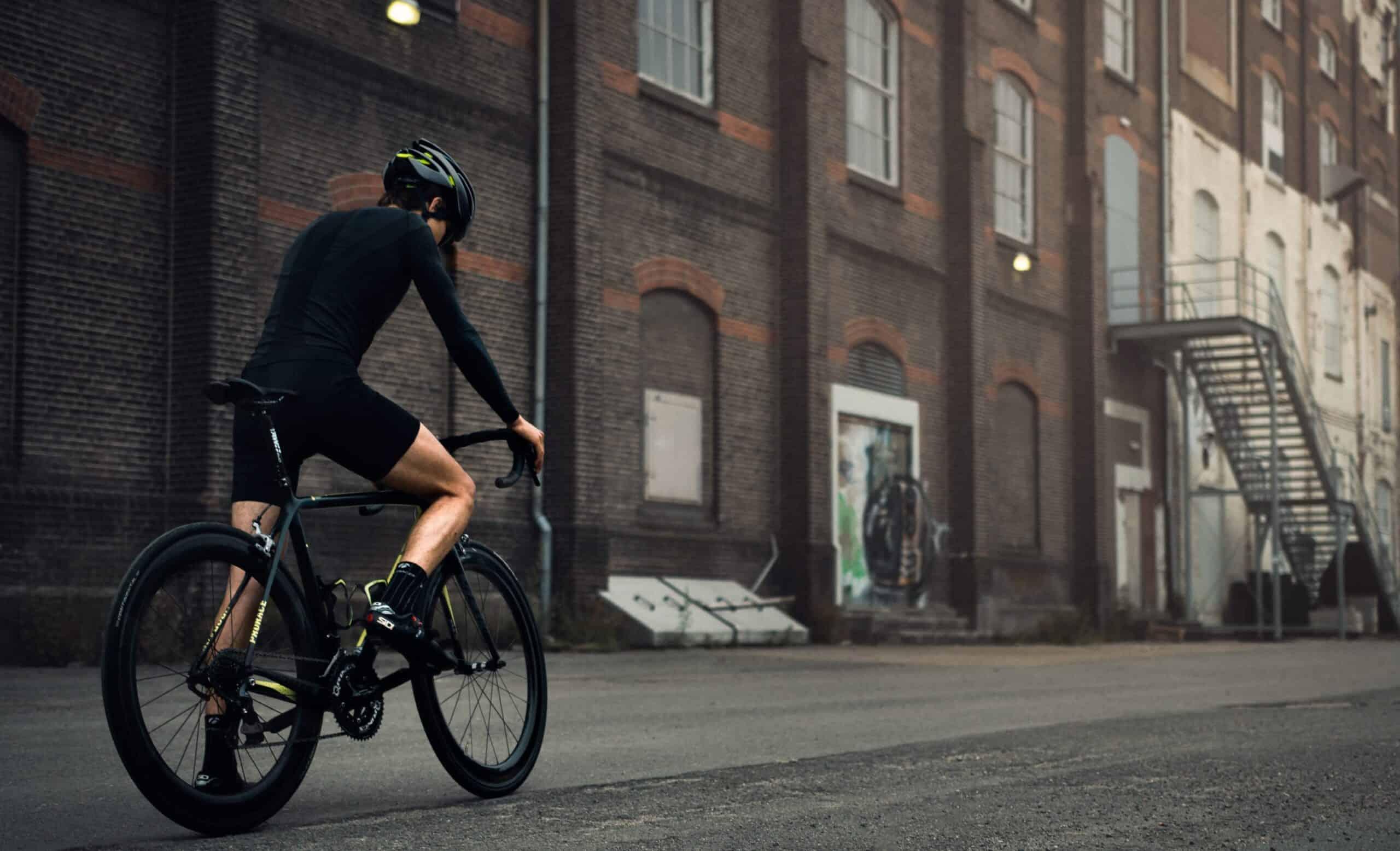 portfolio foto wielrenner met zwarte racefiets in industriële omgeving